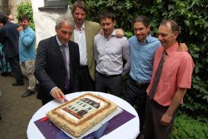 Wolfgang Dorn (li.) schneidet die Jubiläumstorte im Beisein der Gemeindeleitung an.